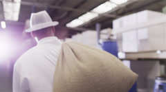 Worker in a coffee processing factory carrying sacks of coffee Stock Footage