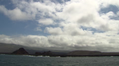 Stock Video Footage of The coast of a volcanic island of the Galapagos, filmed from a boat.