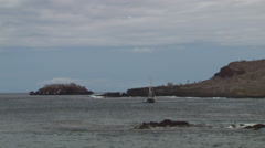 A small boat separates itself from a larger ship near the shore of an island in Stock Footage