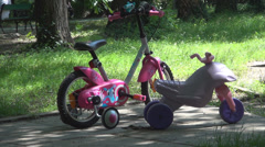 Bicycles left by two childrens at playground, Summer holiday Stock Footage