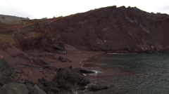 Stock Video Footage of The shore of a volcanic island, where three people are walking in the distance.