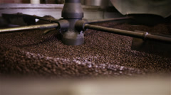 Factory coffee roasting machine in operation, turning and stirring roasted beans - stock footage