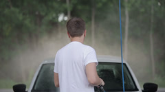 Man in a white t-shirt white car washes. Slow motion Stock Footage