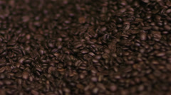 Close up roasted coffee beans being turned & stirred in industrial machine - stock footage