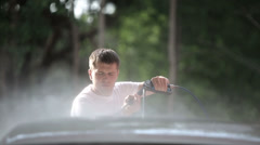 Man in a white t-shirt white car washes. 1920x1080 shot Stock Footage