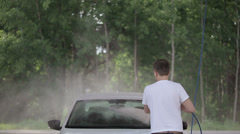 Man in a white t-shirt white car washes with karcher. 1920x1080 shot Stock Footage