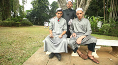 View of a three muslim men posing in the botanical gardens in Kandy. - stock footage