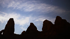 Stock Video Footage of Astrophotography Time Lapse of Moon Rising over Monolithic Formation -Pan Left-