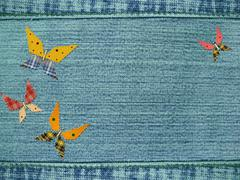 Jeans background with butterflies from rags - stock illustration