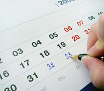 Hand with a pen, adding numbers in a calendar - CONTEST Stock Illustration