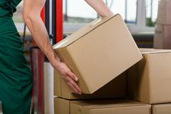 hands of warehouse worker lifting box - stock photo