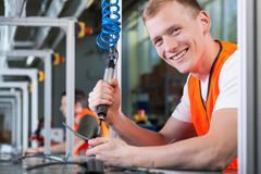 Young smiling man working on the production line Stock Photos