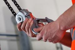 Close-up of male hands and lifting hook Stock Photos