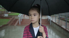 Close up lonely child girl in the rain with an umbrella. Slow motion. Stock Footage