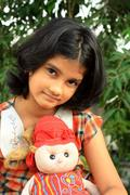 Pretty girl and her beautiful doll Stock Photos