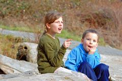 Candid Shot of Big Sister and Little Brother Outdoors Stock Photos