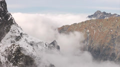 Mountains and thick clouds moving among sharp, rocky peaks Stock Footage