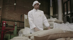 Workers in a factory or warehouse handling large sacks of fresh coffee beans - stock footage