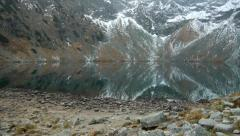A mountain lake (tarn) in November with high mountains reflected in the water Stock Footage
