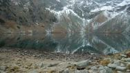 Stock Video Footage of A mountain lake (tarn) in November with high mountains reflected in the water