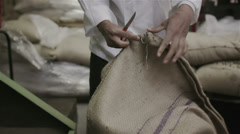 Worker in a factory or warehouse handling large sacks of fresh coffee beans Stock Footage