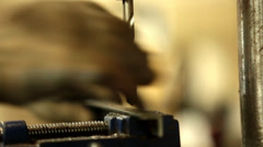 Man working with the drill machine, making precise holes in an iron L bar. Stock Footage