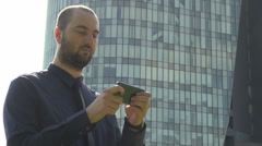 Businessman working outside corporation building texting on the phone sunny day Stock Footage