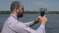 Student well dressed using tablet , working on the lake in the middle of nature Stock Footage
