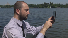 Businessman working in the park, near a lake, stressful, irritated, hard worker - stock footage