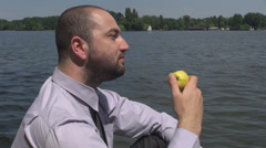 Man eating an golden apple relaxing in the park on a lake side looking around Stock Footage