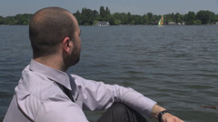 Peaceful quiet calm moments for businessman relaxing near lake looking at boats Stock Footage