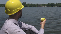 Outside lunch for an young engineer eating an golden apple near a lake sunny day Stock Footage