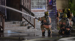 Firefighters extinguishing a building on fire Stock Footage
