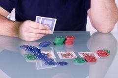 Man Holding Cards on the Table in Texas Hold'em - stock photo