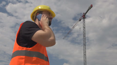 Engineer in site young man talking on phone approving discussion looks at crane  - stock footage