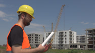 Stock Video Footage of Worker analyzing construction plan papers looking at building stage, approving