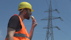 Young man helmet on eating out hamburger in lunch hours near a high voltage pole Stock Footage