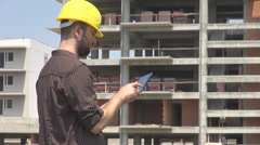Young engineer working on tablet verifying the architecture order construction Stock Footage