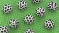 Candy footballs rotating on a green background. Stock Footage