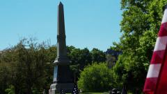 Monument in Cemetery with American Flags Stock Footage