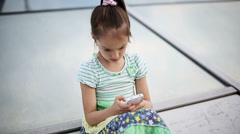 Beautiful child little girl enjoys smartphone. Model Elizabeth Andreeva Stock Footage