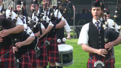 Playing bagpipe band entering Highland Gathering Stock Footage