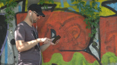 Stylish boy listening music on mobile phone and enjoy playing games on tablet - stock footage