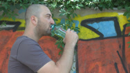 Stock Video Footage of Thirsty young man, graffiti wall background, drinking water looking around chill