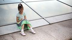 Beautiful child little girl kid enjoys smartphone. Model Elizabeth Andreeva Stock Footage