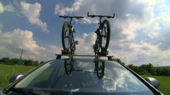 Car driving with two bicycles mounted on bike roof carrier Stock Footage