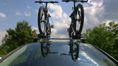 Car with two bicycles on bike roof carrier driving along a country road Stock Footage
