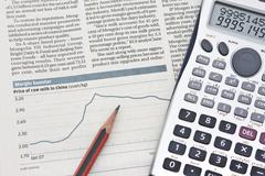 Stock chart with a calculating machine and a pencil. Stock Photos