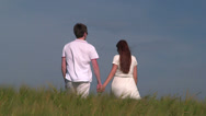 Stock Video Footage of Young couple holding hands and walking through wheat field