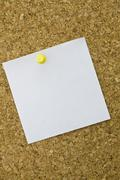 Yellow postit on a everyday corkboard. This is my corkboard. - stock photo